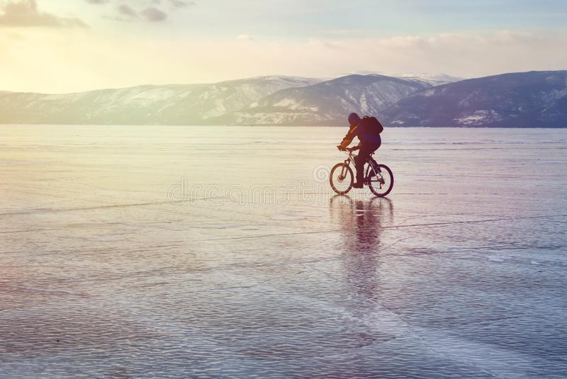 Ice biker traveler with backpacks on bike on ice of Lake Baikal. Against the background of sunset sky, ice surface. Winter sport. Concept. Cycling stock image