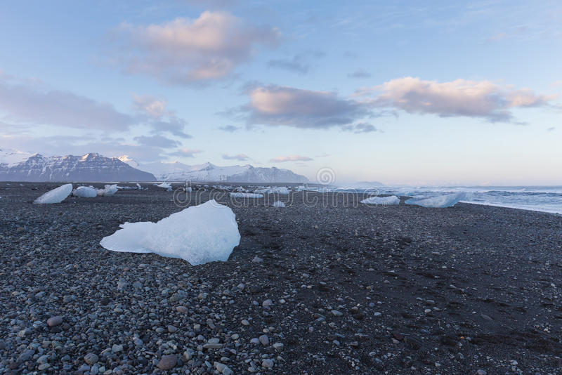 Ice on black rock beach form iceberg skyline in winter season, Iceland. Natural landscape background royalty free stock image