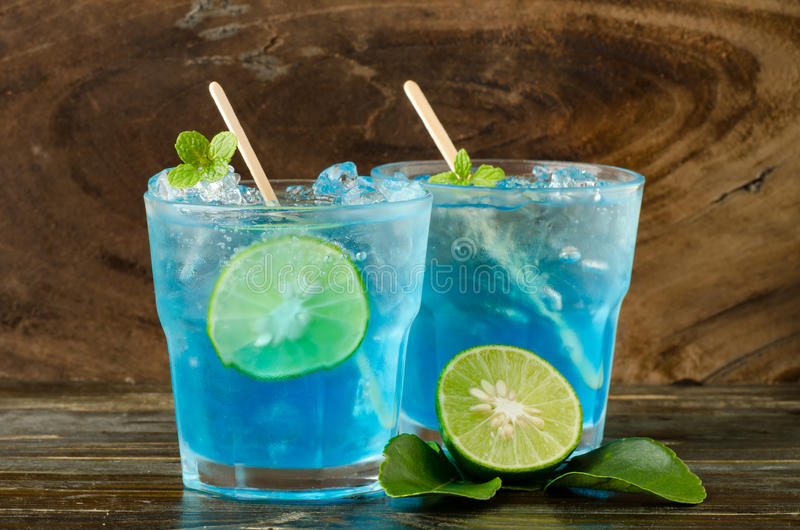 Ice blue drink. With lemon on wooden background stock images