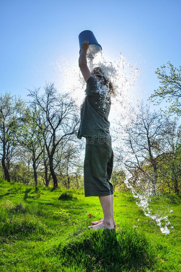 Ice bucket challenge. Man pours iced water from a bucket royalty free stock image