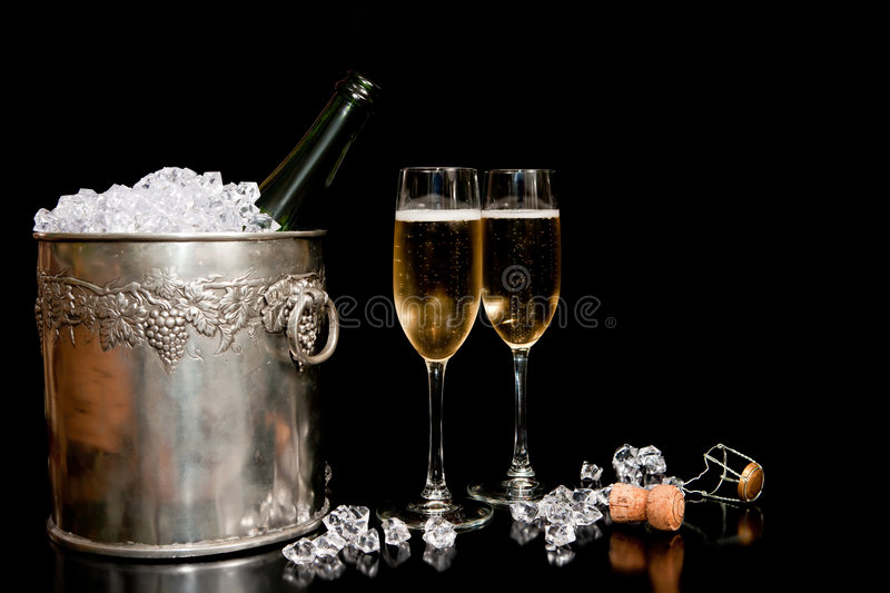 Ice bucket and champagne. A view of a full and overflowing ice bucket chilling a bottle of champagne near two tall champagne glasses on a black background stock images