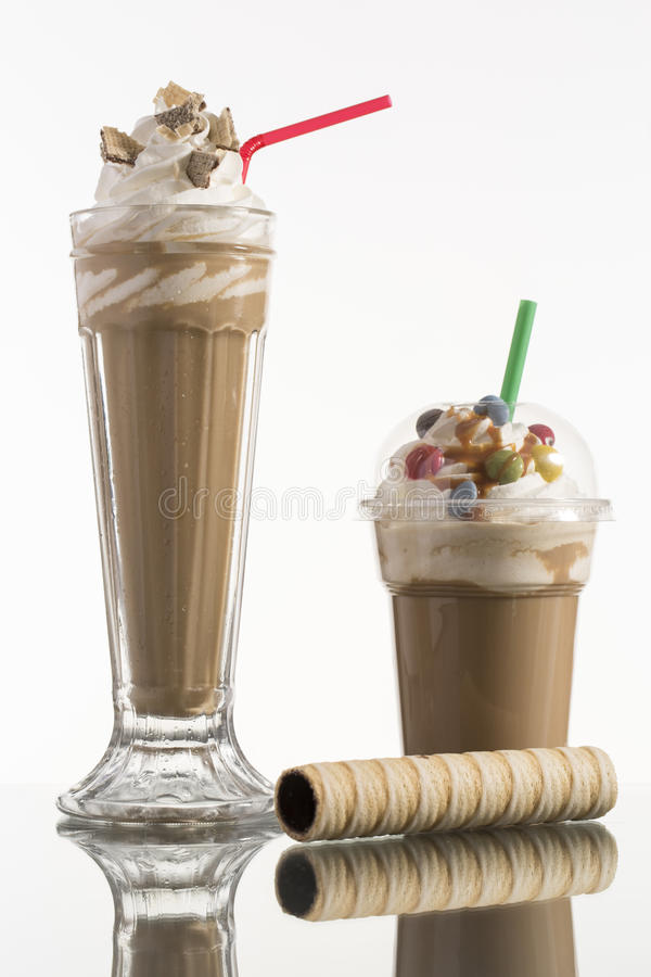 Ice caffe in glass and plastic takeaway cup, decorated with whip stock image
