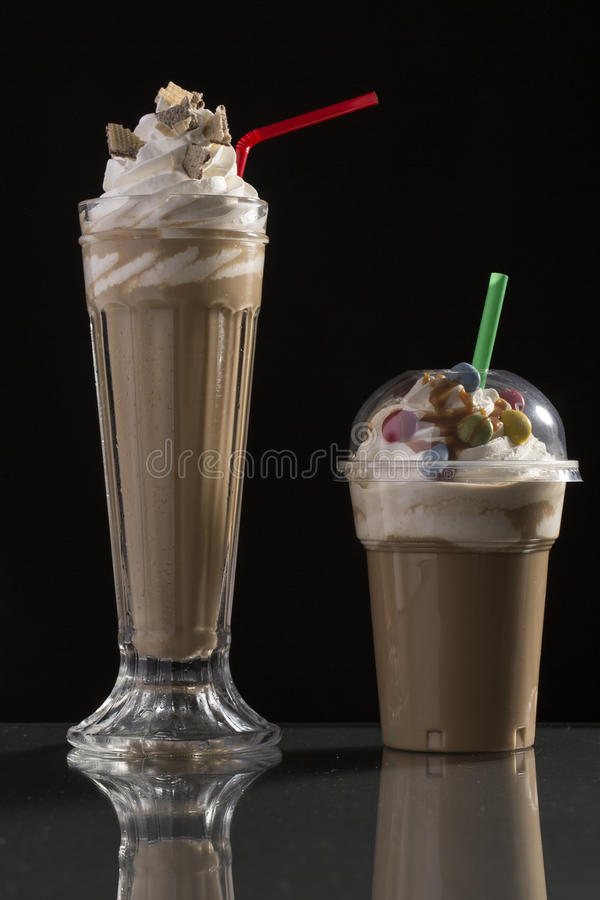 Ice caffe in glass and plastic takeaway cup, decorated with whip stock images