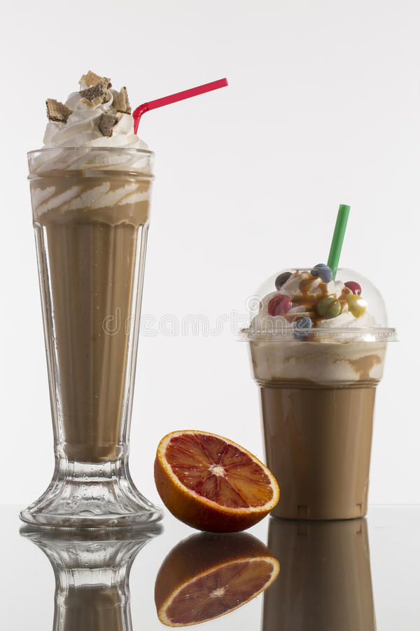 Ice caffe in glass and plastic takeaway cup, decorated with whip stock photos