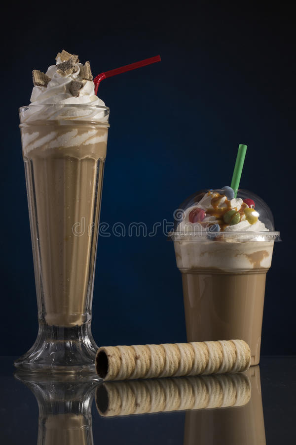 Ice caffe in glass and plastic takeaway cup, decorated with whip stock photography