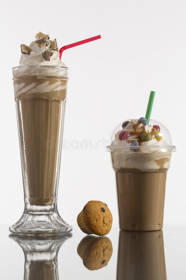 Ice caffe in glass and plastic takeaway cup, decorated with whip royalty free stock photos