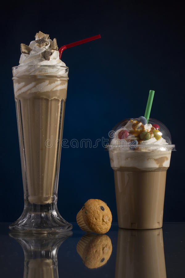 Ice caffe in glass and plastic takeaway cup, decorated with whip royalty free stock photo