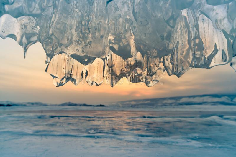 Ice cave close up in Baikal water lake with sunset sky background royalty free stock photography