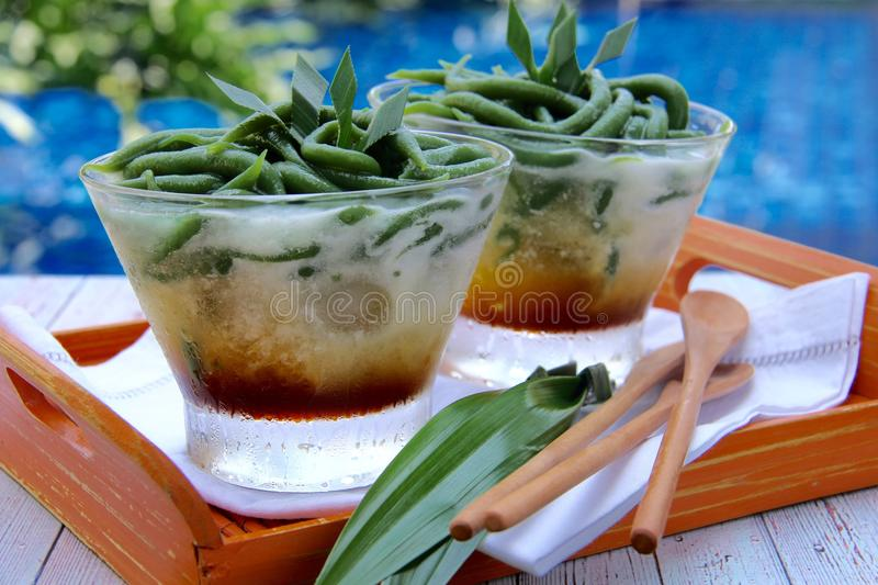Ice Chendol. Traditional dessert drink popular in Southeast Asia, jelly of rice flour and pandanus with coconut milk and palm sugar syrup. Served in oval stock photography