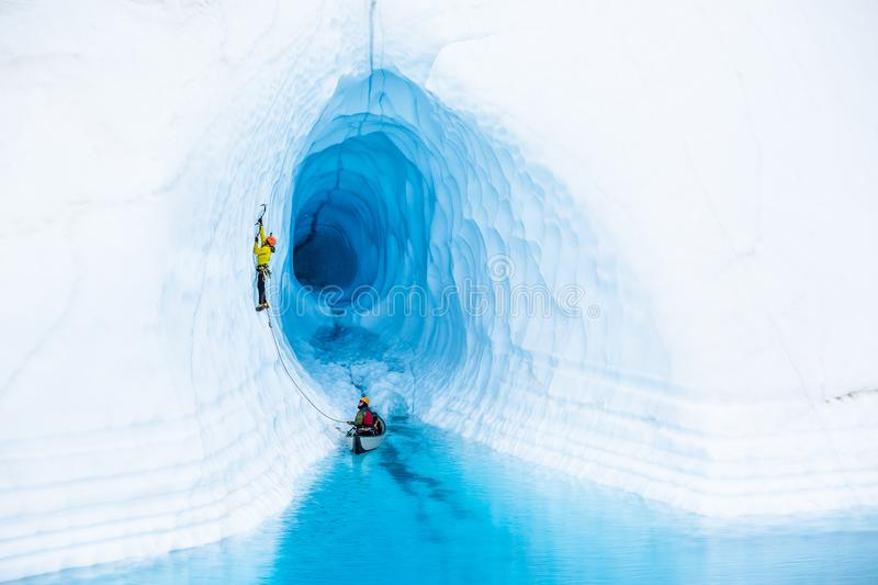 Ice cimber in front of an ice cave leading up from a canoe in a blue pool on the Matanuska Glacier royalty free stock image