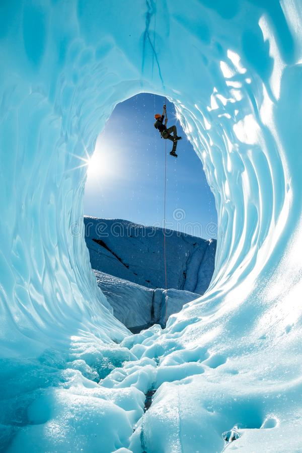 Ice climber ascending a rope over entrance of large blue ice cave on the Matanuska Glacier in Alaska stock images