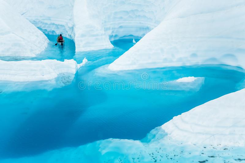 Ice climber boating through winding canyons flooded by glacier water of the Matanuska Glacier in the Alaskan wilderness stock image