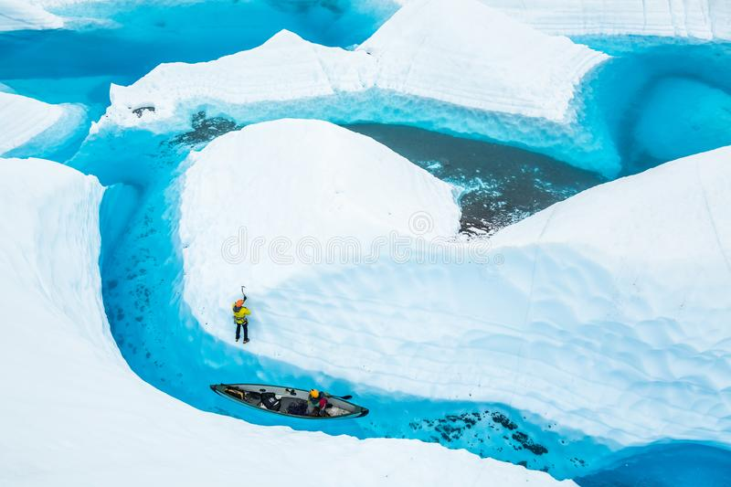 Ice climber and a canoe near an island of ice in a blue pool on the Matanuska Glacier in Alaska royalty free stock photo