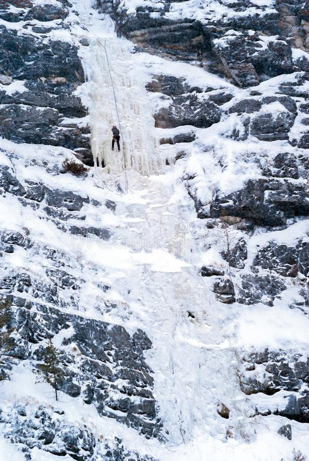 Ice climber climbs on icefall during a snowfall royalty free stock image