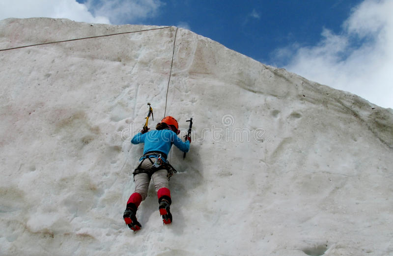 Ice climber with ice axes climbe the wall. Climber on glacier and snow alpinist route, rocky mountain peaks and glacier. Alpinist with equipment - iceaxe stock photo