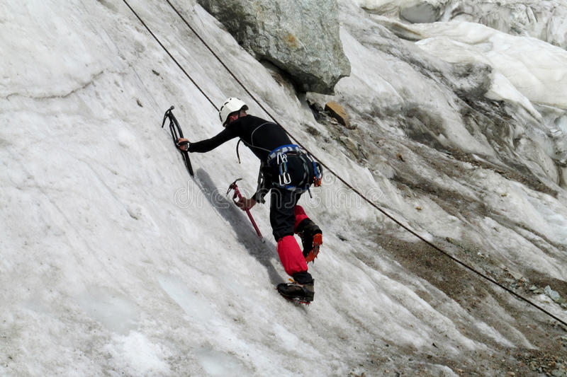 Ice climber with ice axes climbe the wall. Climber on glacier and snow alpinist route, rocky mountain peaks and glacier. Alpinist with equipment - iceaxe stock photos