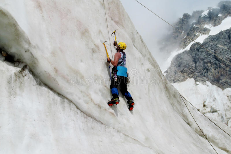 Ice climber with ice axes vertical climbing. Climber on glacier and snow alpinist route, rocky mountain peaks and glacier. Alpinist with equipment - iceaxe stock image