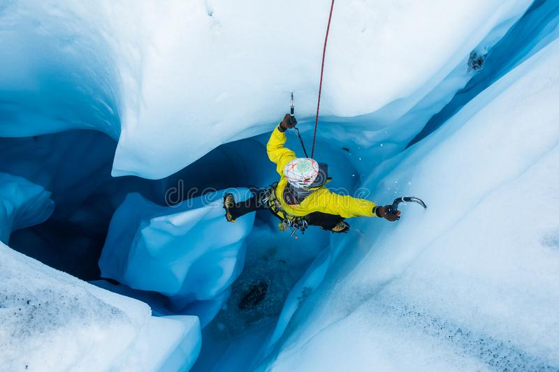 Ice climber on piller inside vertical ice cave on the Matanuska Glacier stock images