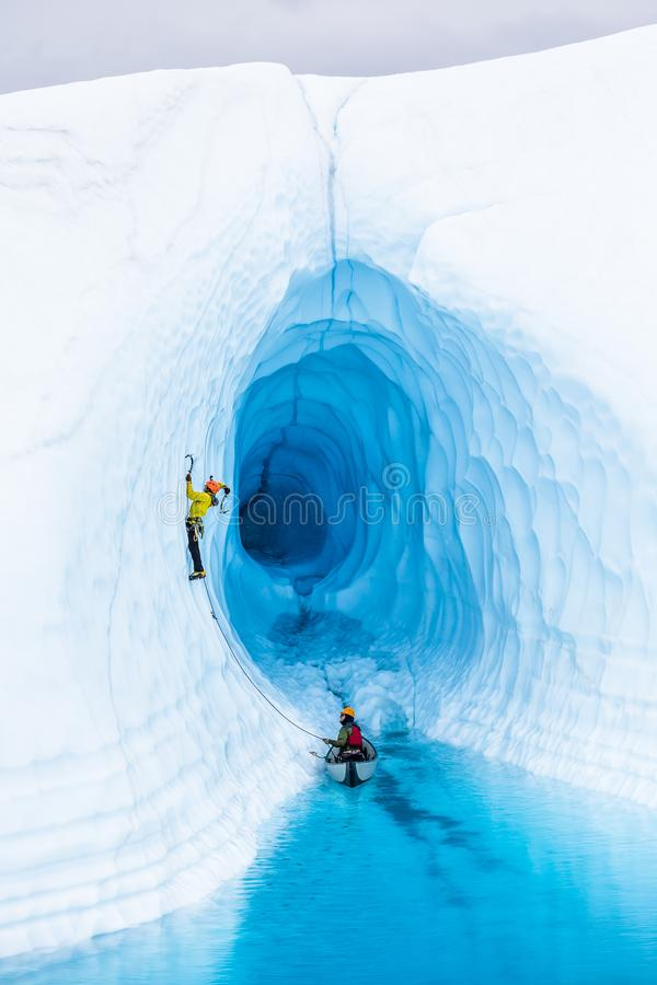 Ice climber swinging ice tool as he leads up the outside of an ice cave on the Matanuska Glacier stock images