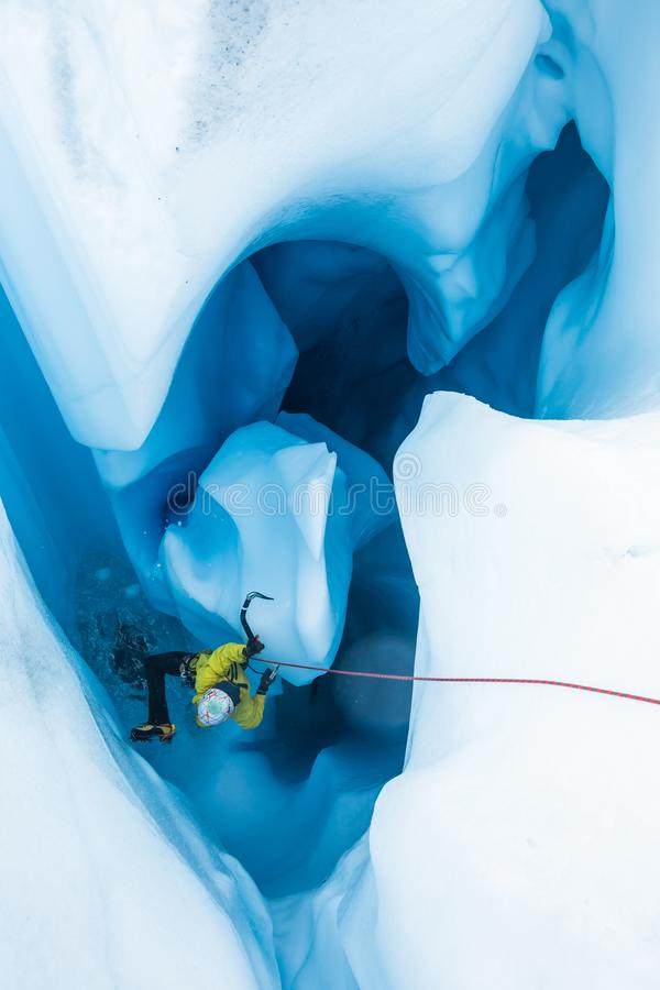 Ice climber in yellow on a massive pillar of ice free standing inside a moulin royalty free stock photos