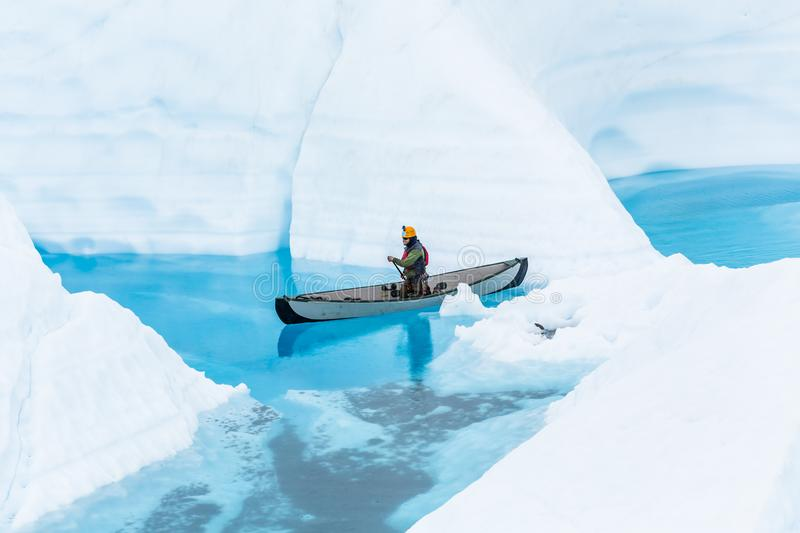 Ice climbing guide on the Matanuska Glacier paddling a canoe through narrow flooded canyons of a glacier lake royalty free stock images