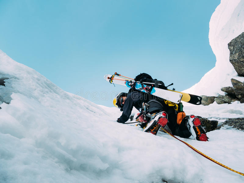 Ice climbing: mountaineer on a mixed route of snow and rock during the winter. Western Alps, Italy, Europe stock photography
