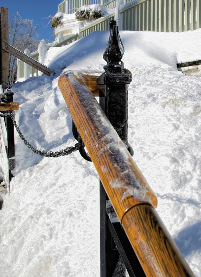 Ice-Coated Wooden Railing at Montmorency Falls. Heavy ice coats a wooden railing and wrought iron post at the Visitors` Center at Montmorency Falls near Quebec stock image