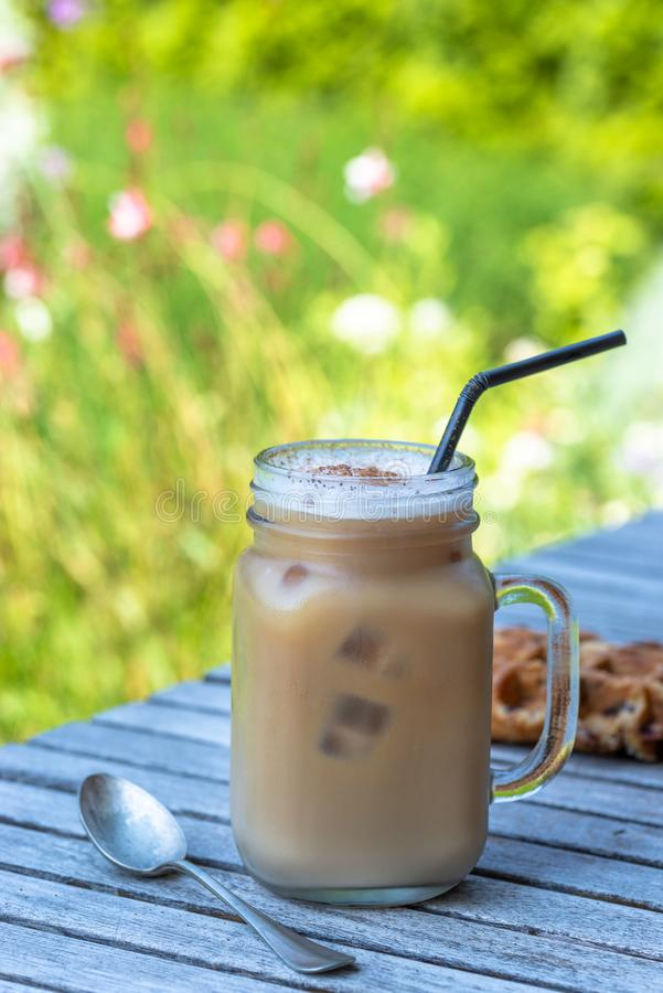 Ice coffee in glass mug with milk and cinnamon on wooden table in the garden. royalty free stock image