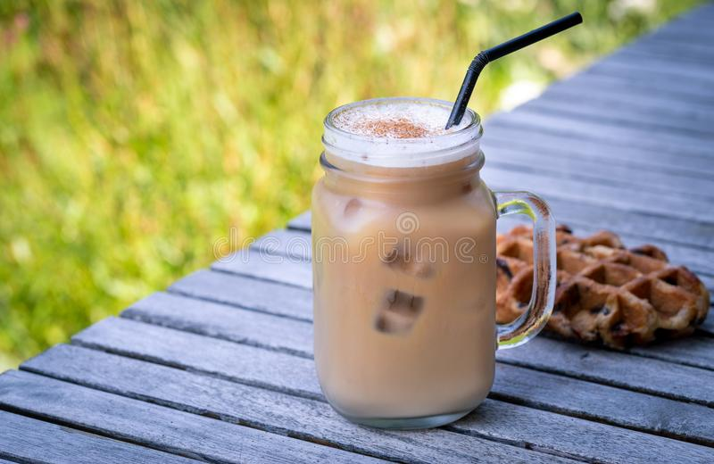 Ice coffee in glass mug with milk and cinnamon on wooden table in the garden. royalty free stock photo