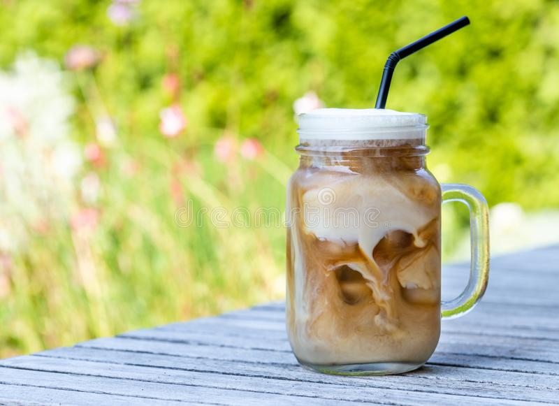 Ice coffee in glass mug with milk and cinnamon on wooden table in the garden. stock photography