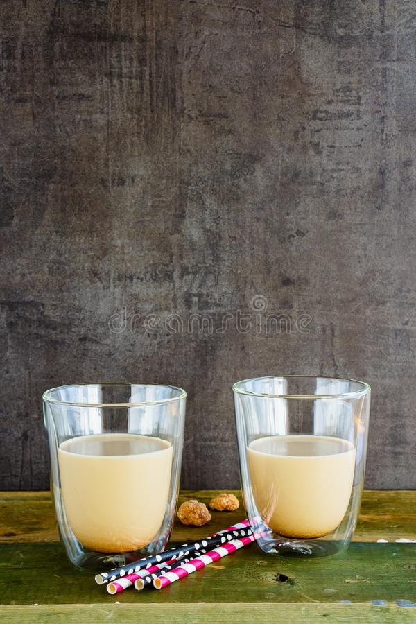 Ice coffee or latte. Cold ice coffee or latte in glass cups on old wooden board, copy space. Dark concrete wall baclground stock image