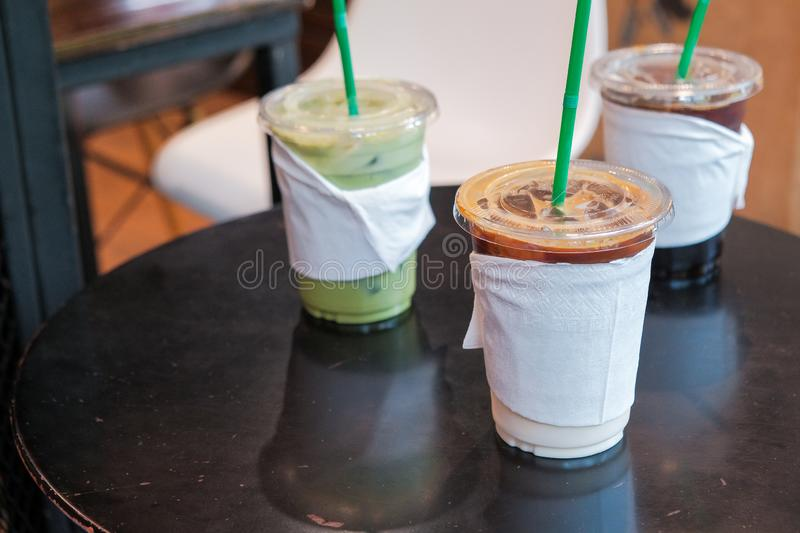 Ice coffee and matcha green tea cold drink in takeaway or to go cup on wooden table. At cafe stock images