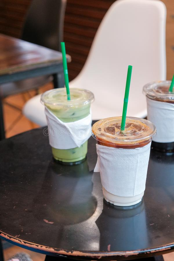 Ice coffee and matcha green tea cold drink in takeaway or to go cup on wooden table. At cafe stock photo