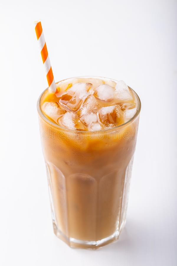 Ice coffee in a tall glass with cream poured over and coffee beans. Cold summer drink on white background.  stock photos