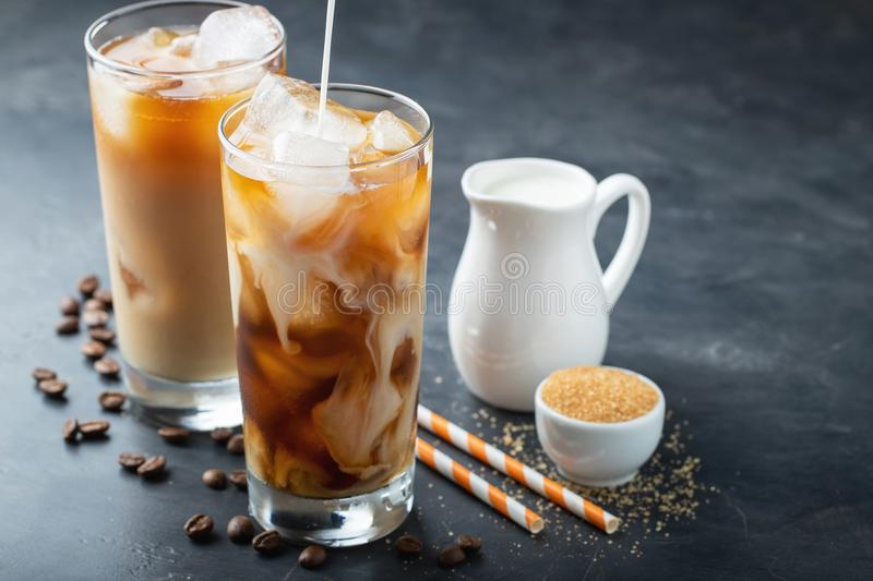 Ice coffee in a tall glass with cream poured over, brown sugar and coffee beans. Cold summer drink on a dark background. With copy stock image