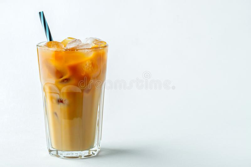Ice coffee in a tall glass with cream poured over and coffee beans. Cold summer drink on a light background. With copy. Space royalty free stock photos