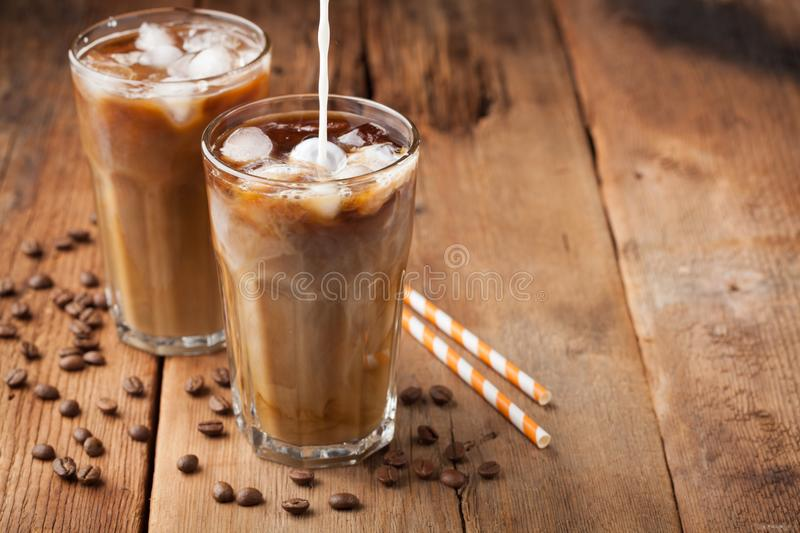 Ice coffee in a tall glass with cream poured over and coffee beans on a old rustic wooden table. Cold summer drink on a dark woode stock image