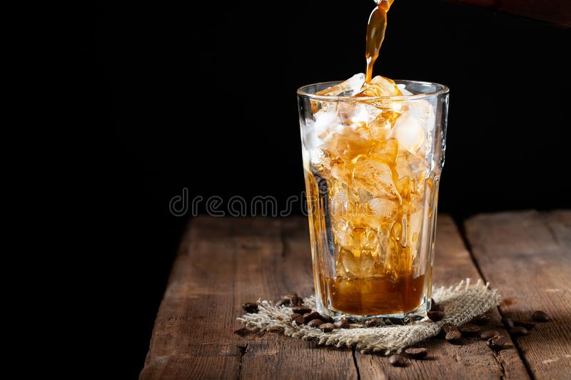 Ice coffee in a tall glass over and coffee beans on a old rustic wooden table. Cold summer drink on a dark background with copy sp stock photo