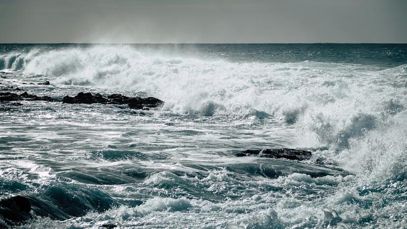 Ice cold water. Waves strike against rocky shallow water. stock image
