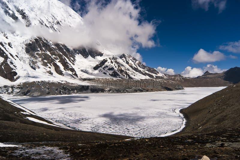 Ice-covered Gebirgssee mit den Wolkenschatten stockbilder