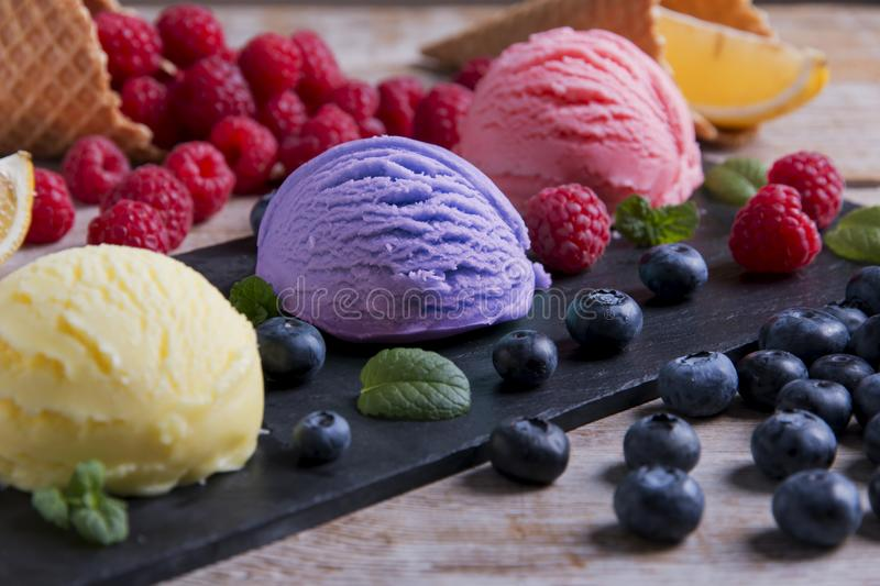 Ice cream assorted balls with lemon raspberry bilberry on a stone surface with pieces of fruit. Delicious fresh fruits ice cream. Summer and Sweet menu a royalty free stock photo