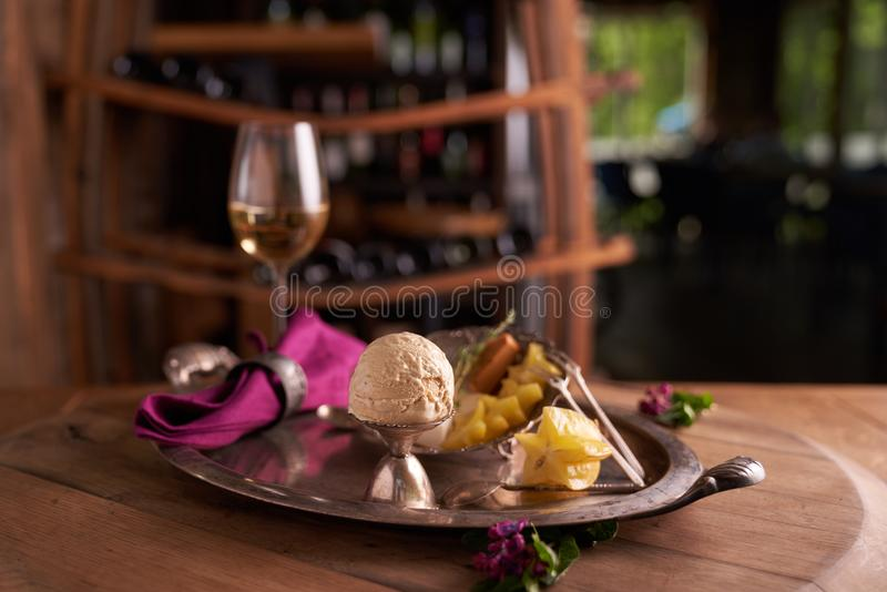 Ice cream ball in an old metal ice-cream bowl on a vintage tray with carambola fruit lying next to it. Behind - a set of cheeses and a glass of white wine royalty free stock photos