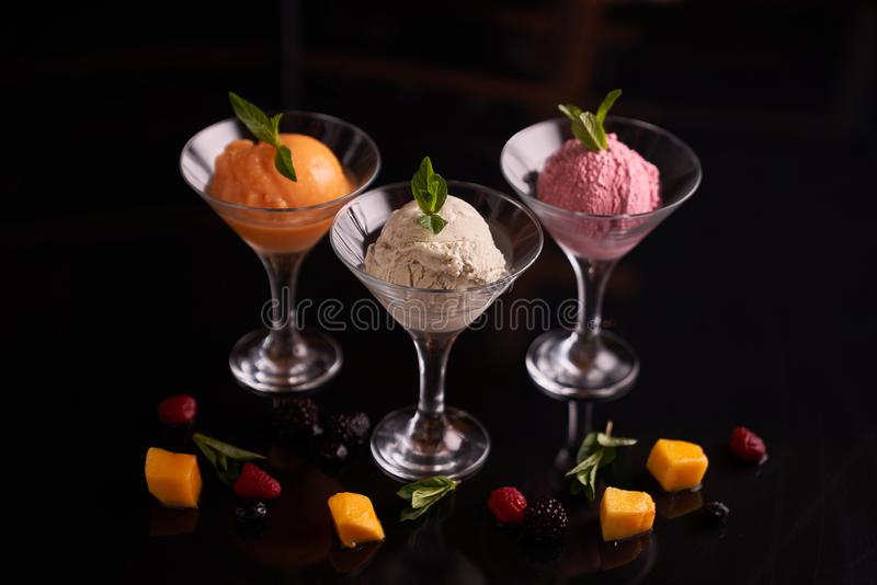 Ice cream with beets, mango, mascarpone cheese in glass ice-cream bowls, decorated with mint leaves on a dark background royalty free stock images