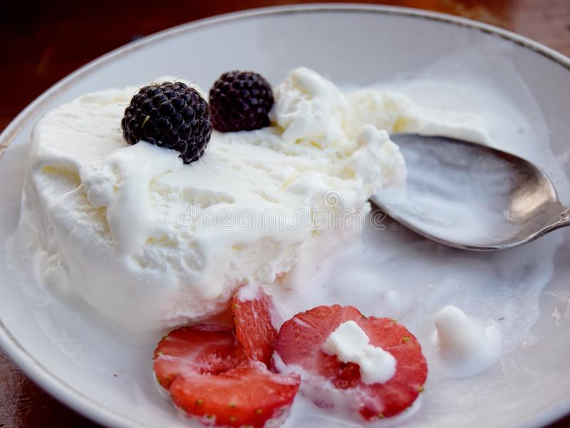 ice cream with blackberries and strawberries with spoon closeup stock photo