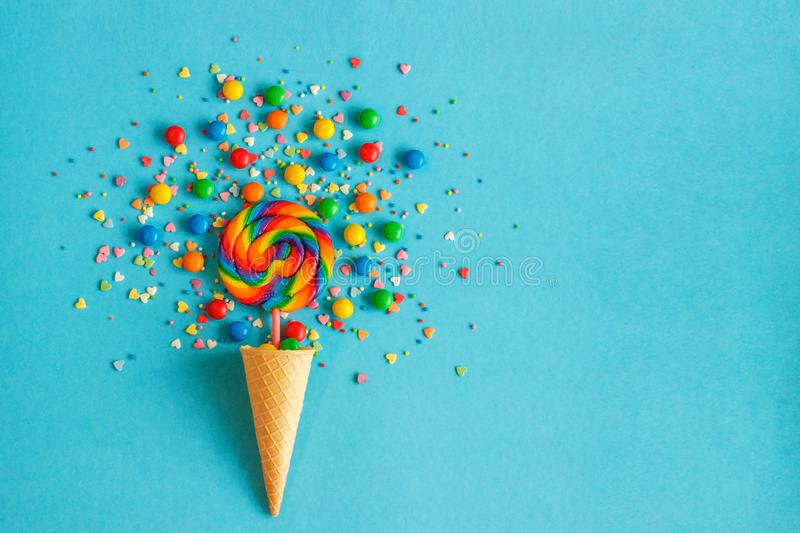 Ice cream cone with colorful lollipop and multicolored sweets. Ice cream waffle cone with colorful lollipop on stick, scattering of multicolored sweets and royalty free stock image
