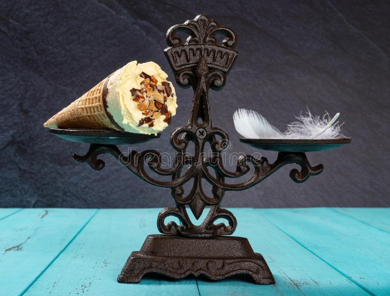 Ice cream cone and feather on balanced scale concept of non fat ice cream. Ice cream cone and feather on a balanced scale concept of non fat ice cream royalty free stock images