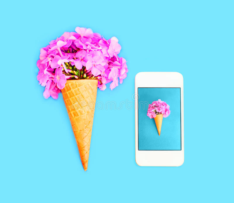 Ice cream cone with flowers and smartphone over blue colorful. Background top view royalty free stock images