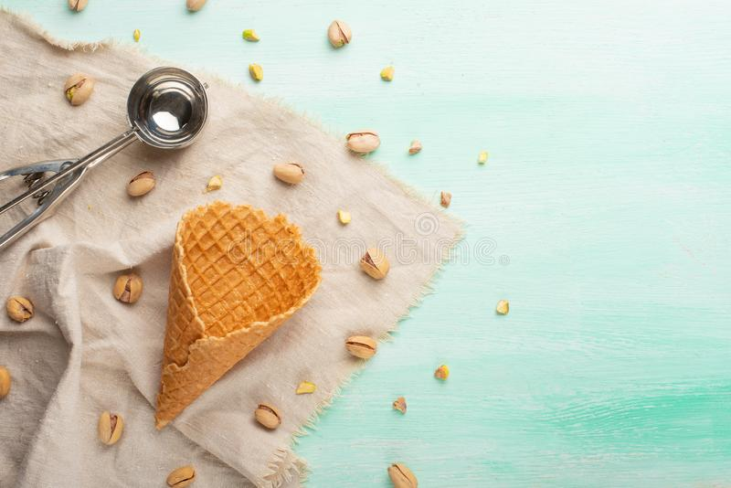 Ice cream cone on mint background with ice cream spoon and pistachio nuts. With space.  royalty free stock images