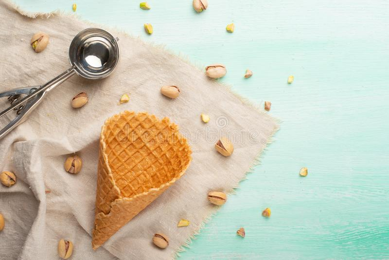Ice cream cone on mint background with ice cream spoon and pistachio nuts. With space.  royalty free stock photos