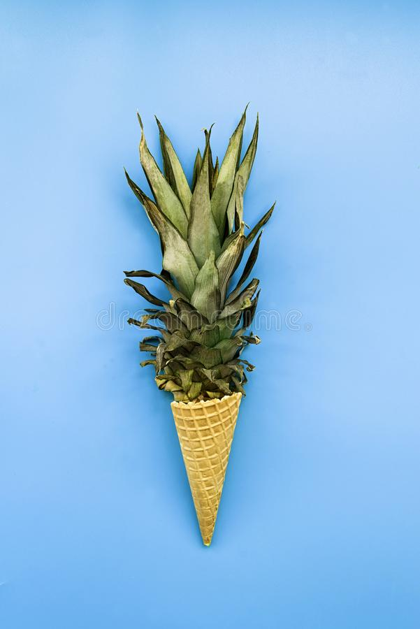 Ice cream cone with pineapple leaves on pastel blue background flat lay top view stock photo